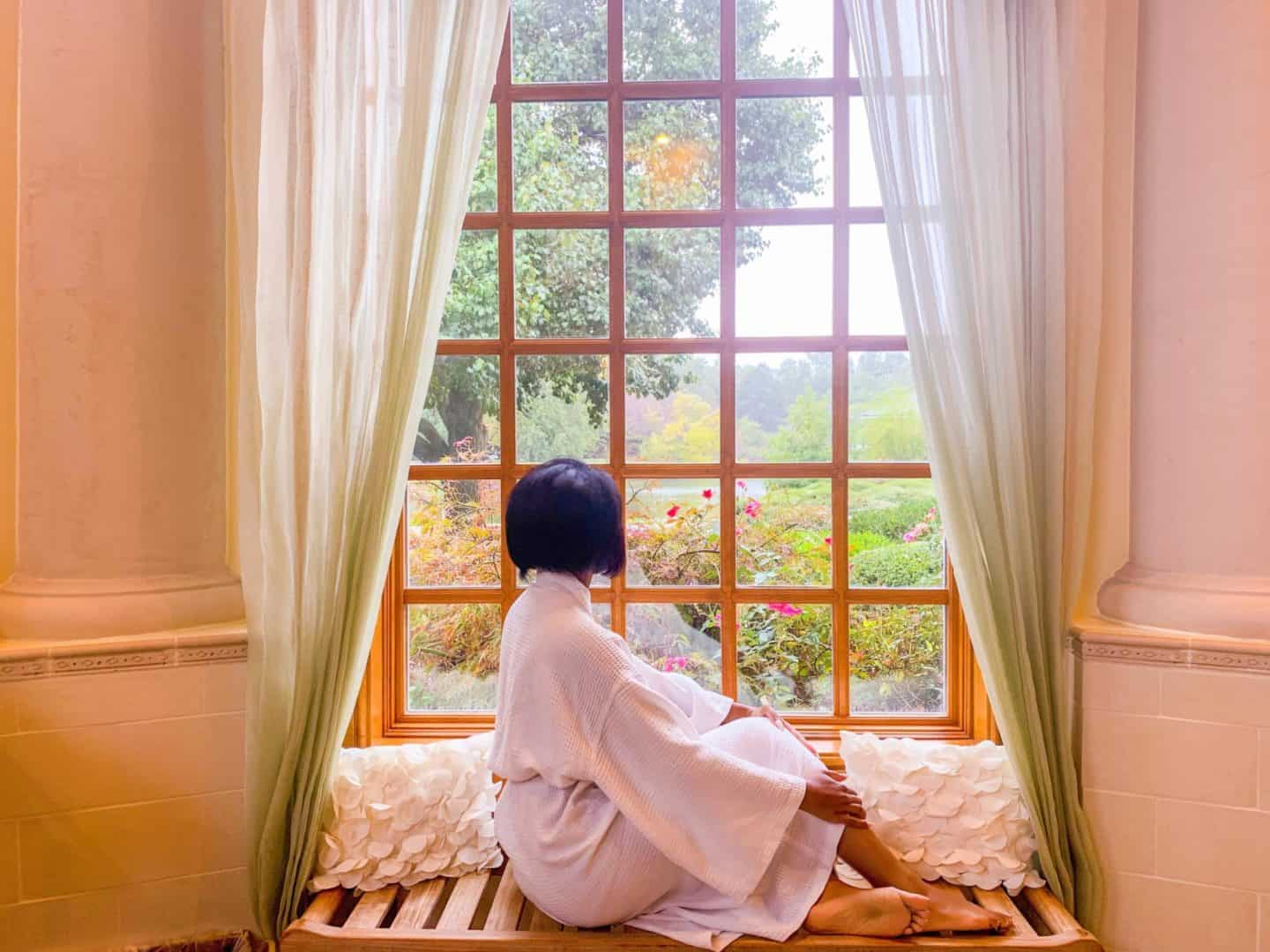 woman sitting in a window nook Fibroid removal surgery recovery time